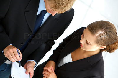 Buy stock photo Cropped shot of two colleagues discussing some ideas