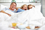 Excited family lying together on the bed at home