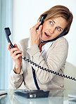 Pretty lady talking on both telephone and mobile phone at her de