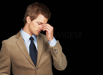 Buy stock photo Stressed out young business man over black background
