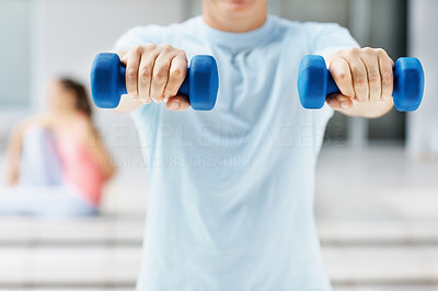 Mid section of a man using dumbbells at the gym
