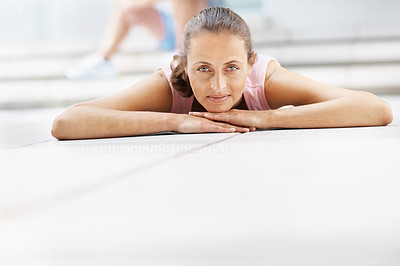 Happy mature woman lying on the floor at the gymnasium