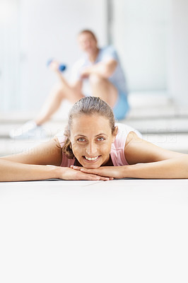 Happy pretty female at the gymnasium lying on the floor