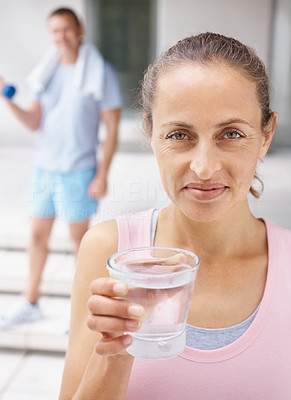 Happy mature female with a glass of water at the gymnasium