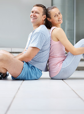 Smiling couple sitting back to back at the gym