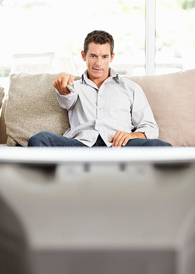 Middle aged man holding remote control while watching television