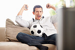 An excited middle aged man watching football match on television