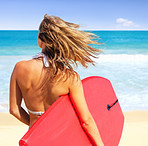 Back view of woman holding surfboard at the beach