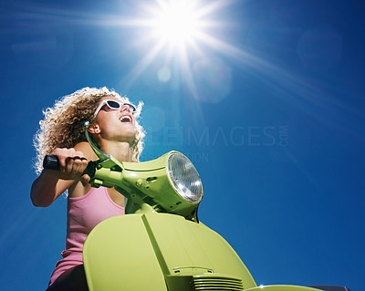Buy stock photo Closeup portrait of young woman with curly hair riding a scooter on a sunny day - Outdoor