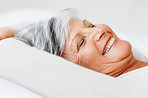 Relaxed elderly woman smiling in bed