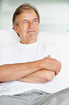 Relaxed old man looking away in a thought