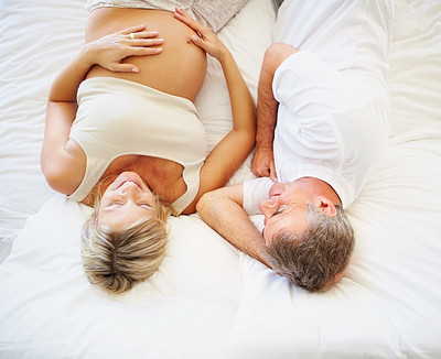 Happy mature pregnant woman with her husband lying on bed