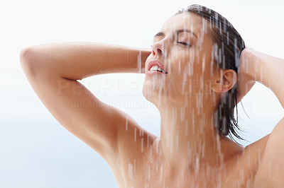 Young woman bathing under an outdoor shower
