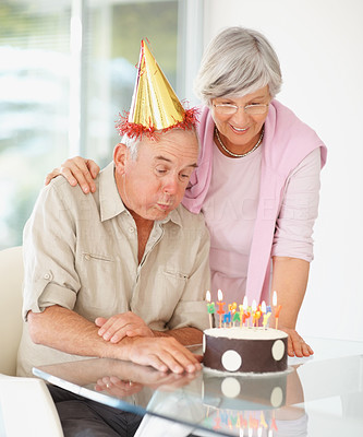 Senior man blowing out birthday candles on his birthday