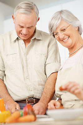 Retired older couple preparing food together in the kitchen