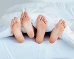View of a couple's bare feet sleeping in bed