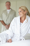 Happy mature woman sitting on bed with husband at the back
