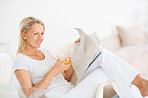 Mature woman enjoying glass of juice while reading newspaper
