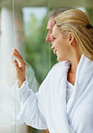 Happy mature woman with her husband looking through glass wall