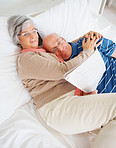A loving senior man and woman reading newspaper on bed