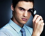 Thoughtful young business man holding glasses