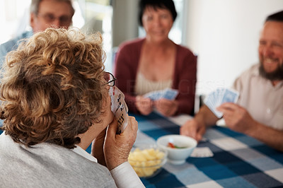Elderly woman playing a game of cards with friends