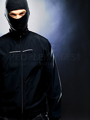 Buy stock photo Portrait of a male terrorist standing wearing balaclava against dark background