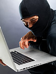 Cyber crime - Male hacker stealing information from laptop