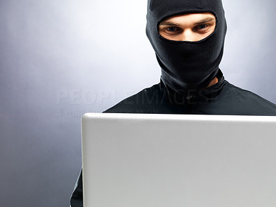 Buy stock photo Portrait of a young male thief stealing data from laptop