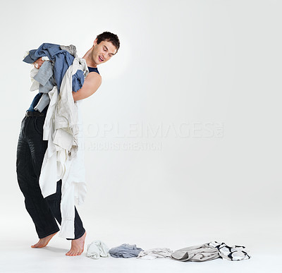 Buy stock photo Portrait of a happy young male carrying clothes to laundry with some clothes falling down - Copyspace