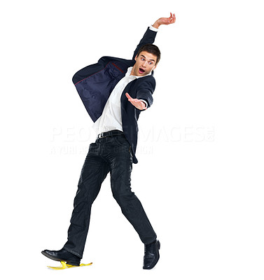 Buy stock photo Portrait of a smart young male entrepreneur slipping on banana peel over white background
