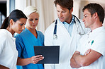 Medical practitioners discussing on a report of a patient