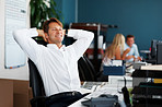 Businessman relaxing at desk with colleagues in background