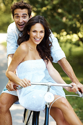 Buy stock photo Cropped shot of a young couple cycling in the park