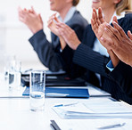Business people clapping hands at a seminar, focus on glass on table