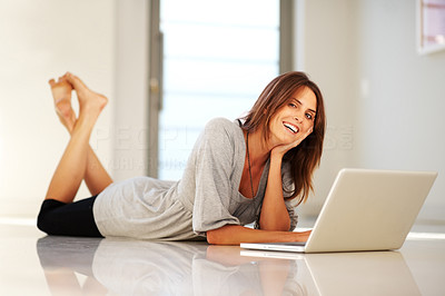 Buy stock photo Smiling young woman lying on floor with a laptop