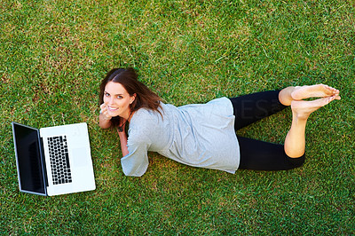 Buy stock photo Relaxed young woman lying down on the grass using