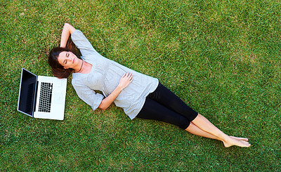 Buy stock photo Beautiful young woman resting on grass with laptop