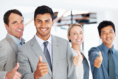 Happy business team giving thumbs up
