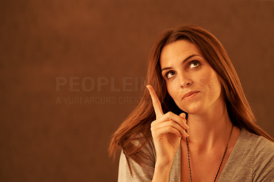 Buy stock photo Young lady pointing at copyspace against brown bac