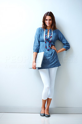 Buy stock photo Pretty young female model posing with a laptop against a white wall next to copyspace