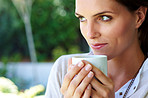 Cute young woman looking away with a coffee cup