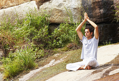 Young man practicing yoga with his hands raised