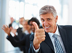 Business man showing a thumbs up with happy staff in the background