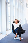 Happy business woman relaxing on a chair at the hallway