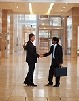 Successful business men greeting eachother at a hallway
