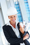 Portrait of a successful female architect in a hardhat smiling
