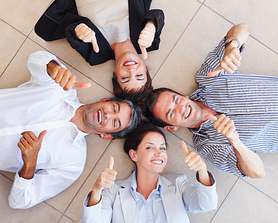 Business people lying in a circle on the floor with their thumbs up