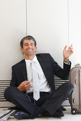 A happy business man enjoying music and smiling