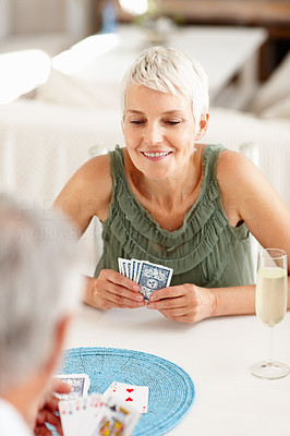Senior woman playing a game of cards with a person